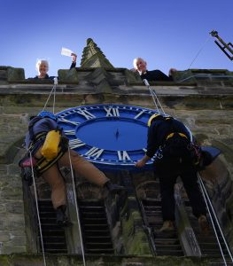 Tony Davies, Smith of Derby clockmaker applying double thickness English gold leaf to the north face of St James Church, Barton under Needwood. Rev'd Andrew Ridley and Julie Skinner at the top of the tower. With rope access @jasonbudd West Country Access.